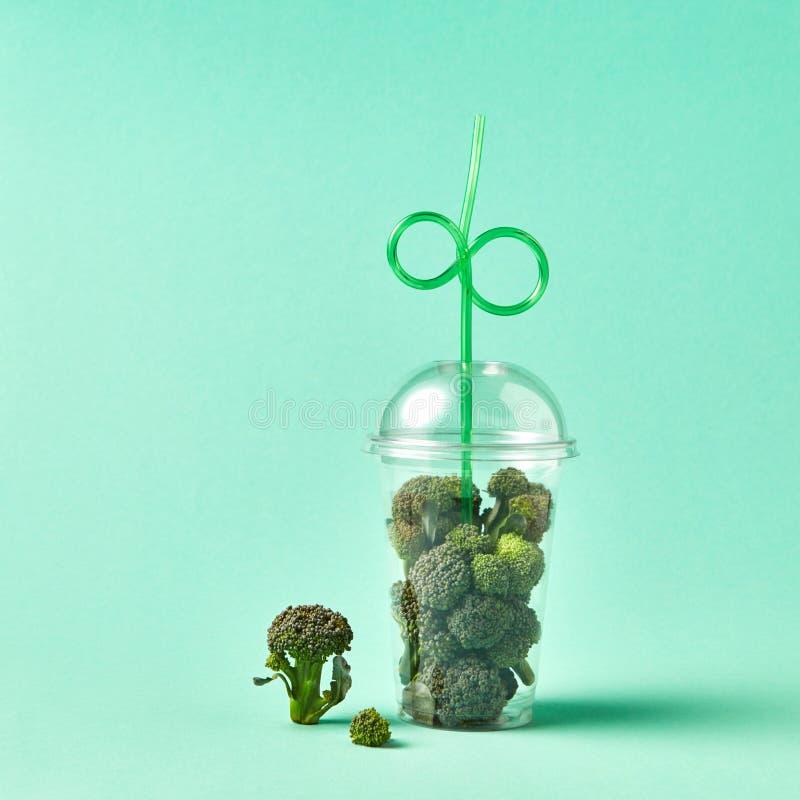 Zdrowi zieleni organicznie surowi brokułów florets w plastikowej filiżance z słomą na zielonym pastelowym tle obraz stock