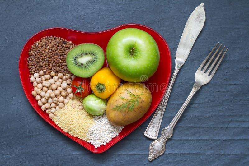 Zdrowia jedzenie na czerwonym serce talerza diet abstrakta wciąż życiu obraz stock