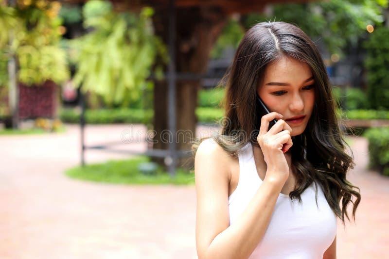 Zdrowie bawją się młodej kobiety pisać na maszynie wiadomość tekstową na mądrze telefonie i zdjęcie royalty free