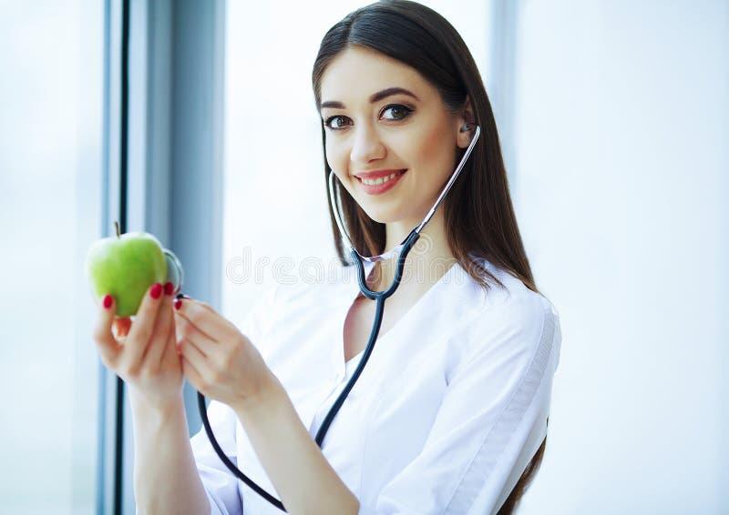 Zdrowie i piękno Doktorska dietetyczki pozycja blisko okno przy Lekkim biurem Dziewczyna Trzyma Apple w rękach I uśmiechach zdjęcia royalty free