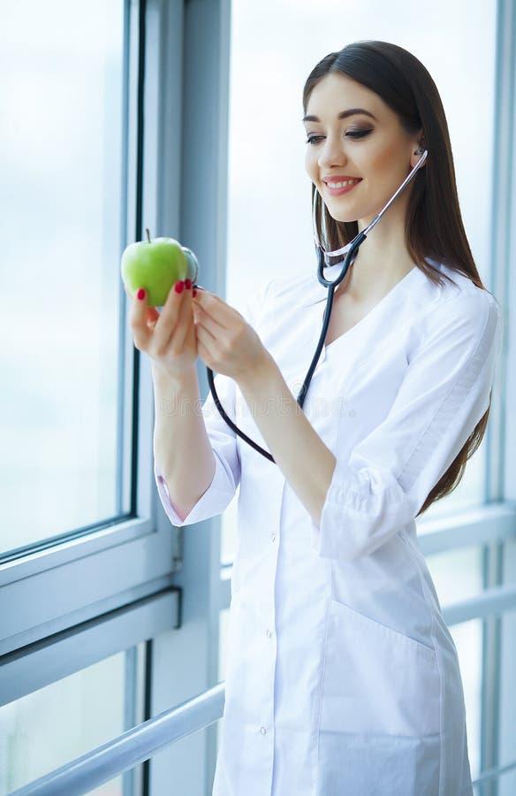 Zdrowie i piękno Doktorska dietetyczki pozycja blisko okno przy Lekkim biurem Dziewczyna Trzyma Apple w rękach I uśmiechach obraz royalty free
