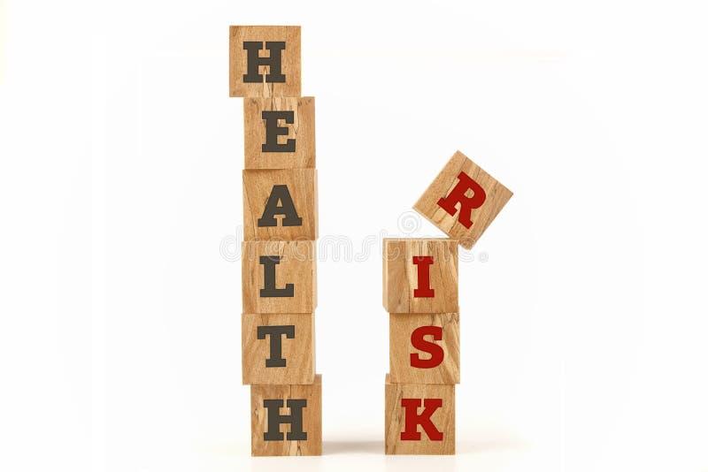 Zdrowie i ryzyka słowo pisać na sześcianie kształtuje zdjęcia stock