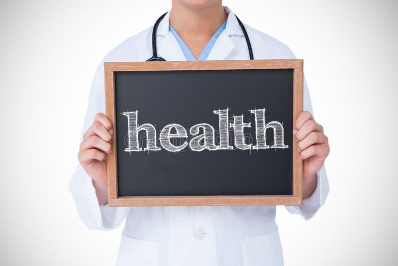 Zdrowie przeciw lekarce pokazuje małego blackboard obraz stock