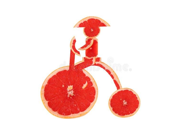 Zdrowy łasowanie. Śmieszny rocznika rower robić grapefruitowy slic obrazy royalty free