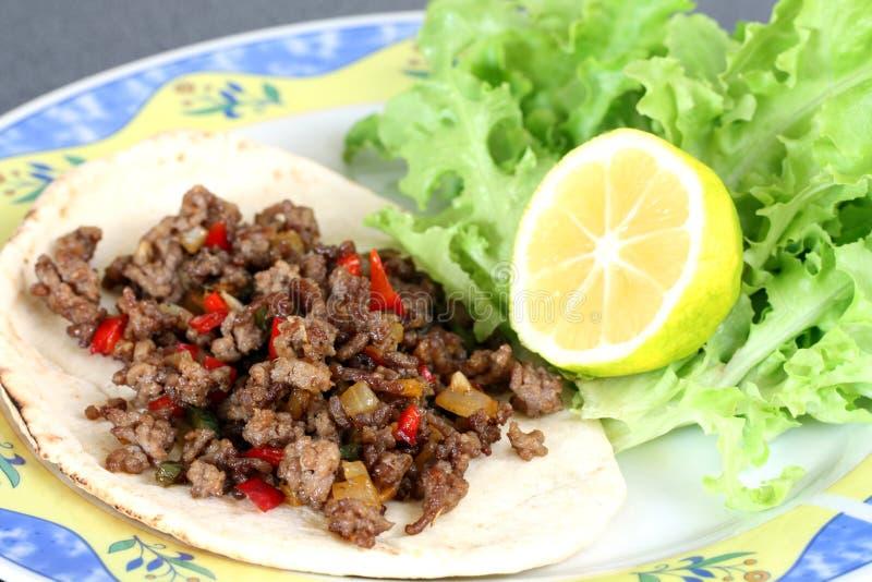Zdrowy łasowanie: piec na grillu wołowiny taco z warzywami, sałatką i cytryną, zdjęcie royalty free