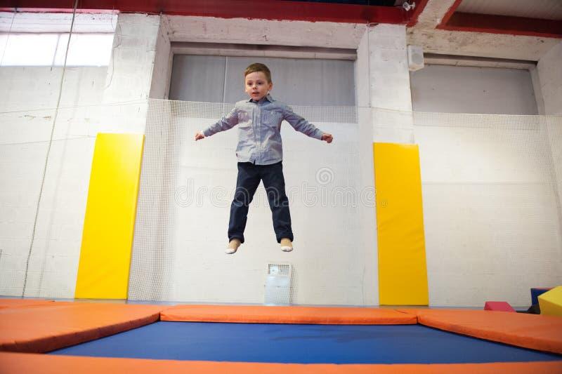 Zdrowy śliczny chłopiec doskakiwanie na trampoline indoors w sporta centre zdjęcie royalty free
