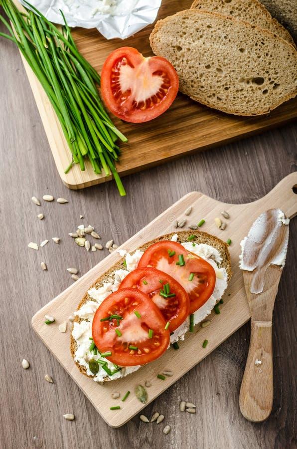 Zdrowy śniadanie - domowej roboty piwny chleb z serem, pomidory zdjęcia stock