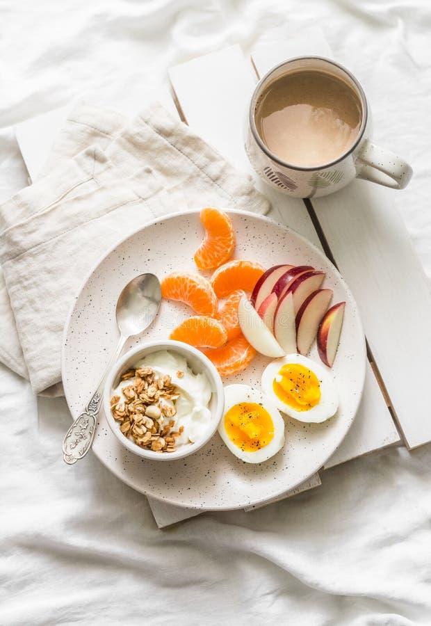 Zdrowy śniadanie - jogurt z granola, świeżej owoc jabłkami, tangerines i kawą z mlekiem na lekkim tle, fotografia royalty free