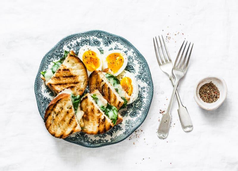 Zdrowy śniadanie lub przekąska - gotowani rolni jajka, szpinak, piec na grillu ser ściskają na lekkim tle zdjęcie royalty free