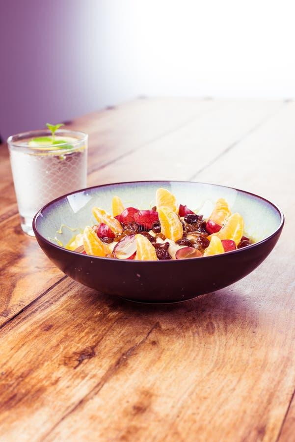 Zdrowy śniadanie na drewnianym stole - woda z cytryną i owsianką z owoc i miodem zdjęcia royalty free