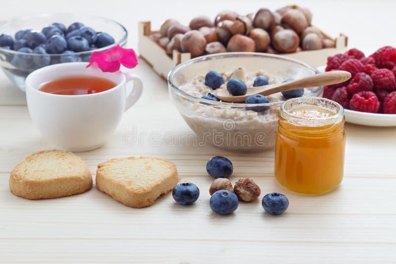 Zdrowy śniadanie oatmeal, czarne jagody, malinki, hazelnuts, herbata z miodem i ciastka, obrazy stock