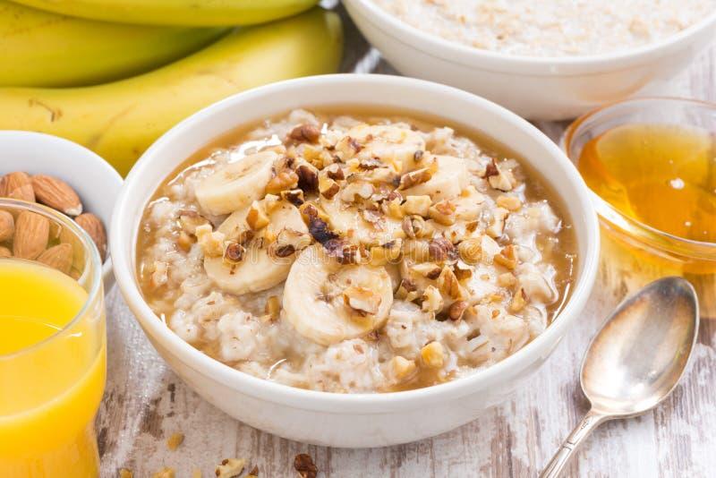 Zdrowy śniadanie - oatmeal z bananem, miodem i orzechami włoskimi, obraz royalty free