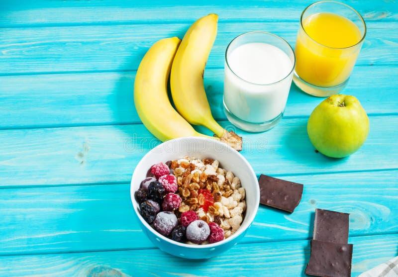 Zdrowy śniadanie - Oatmeal z owoc, mlekiem i sokiem przy błękita stołem, obraz stock