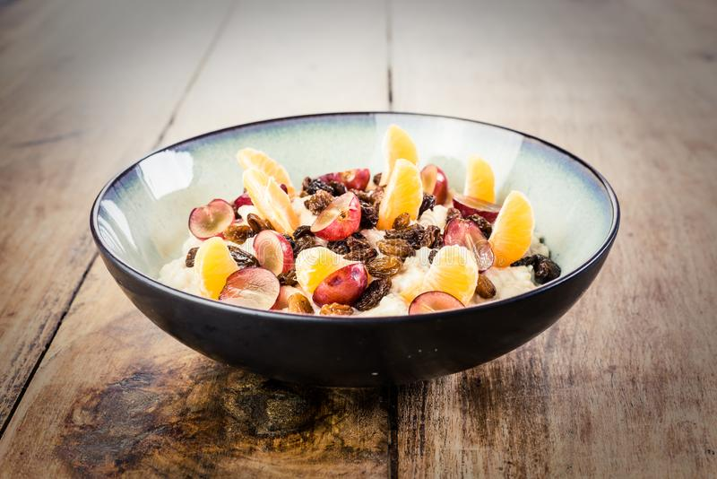 Zdrowy śniadanie - owsianka z świeżą owoc i rodzynkami na drewnianym stole zdjęcie stock