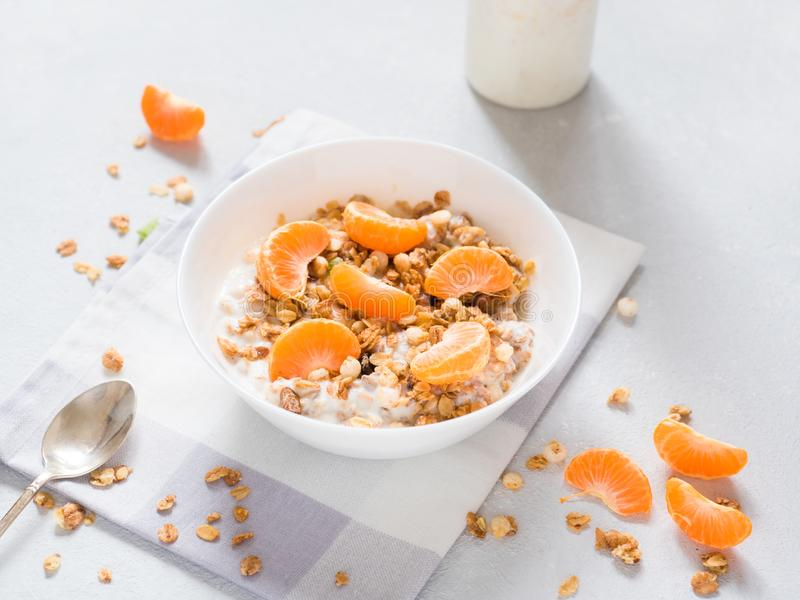 Zdrowy śniadanie Piec muesli z tropikalnymi owoc, świeżymi tangerines i jogurtem na białym tle, zdjęcia stock