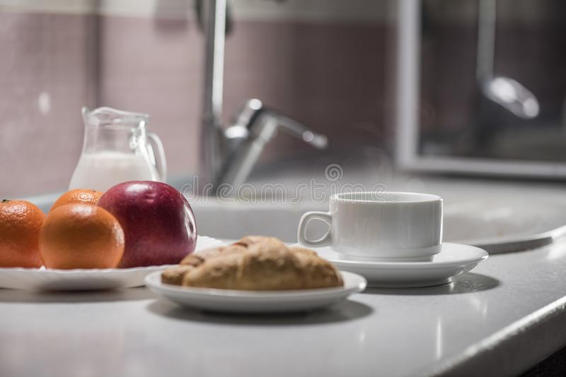 Zdrowy śniadanie w kuchni z kawą, croissants, mlekiem i owoc, obraz royalty free
