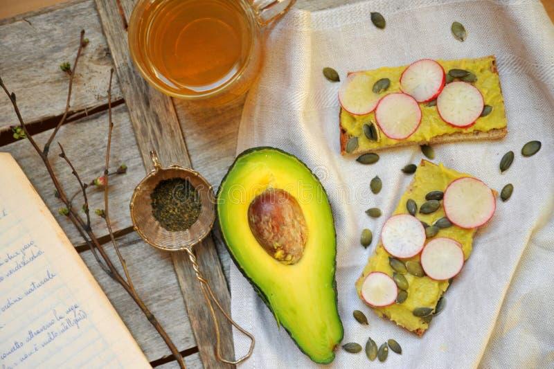 Zdrowy śniadanie z avocado i chickpea pesto z herbatą fotografia stock