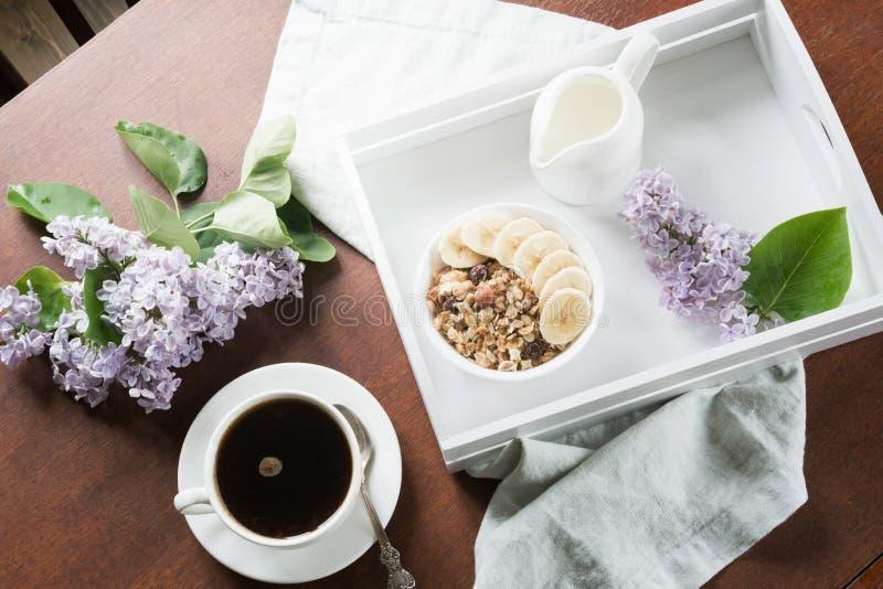 Zdrowy śniadanie z filiżanką kawy, muesli, bananami i wystrojem z kwiatami bez w dom na wsi, zdjęcie stock