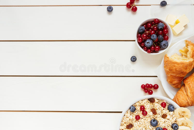 Zdrowy śniadanie z owsów płatkami, jagody, croissants na białym drewnianym stole z kopii przestrzenią, odgórny widok obraz royalty free