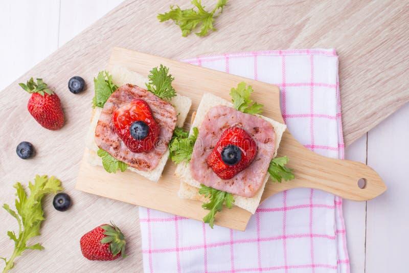 Zdrowy śniadanie z wznoszącym toast chlebem, baleron, warzywa, strawberr fotografia royalty free