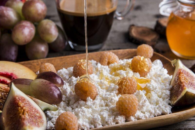 Zdrowy śniadaniowy chałupa ser, malinki, figi, brzoskwinia, miód, kawa na porci desce nad nieociosany drewnianym obrazy stock