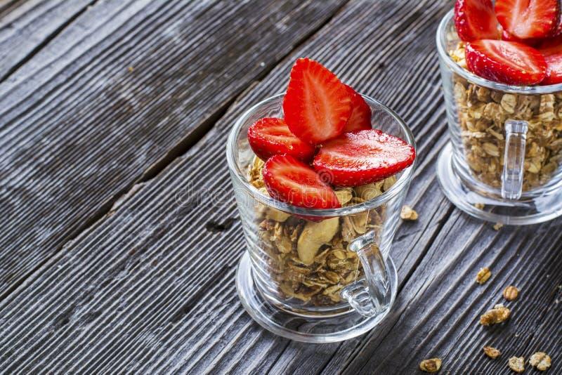 Zdrowy śniadaniowy deser Domowy crunchy granola z dokrętkami i świeżymi truskawkami zdjęcia royalty free