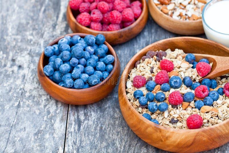 Zdrowy śniadaniowy muesli z jagodami i mlekiem w drewnianym talerzu obraz stock