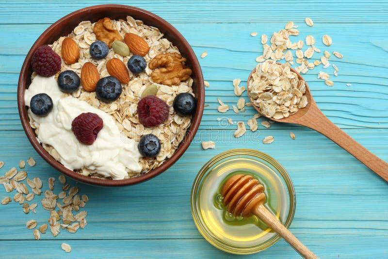 zdrowy śniadaniowy oatmeal, miód, czarne jagody, malinki i dokrętki na błękitnym drewnianym stole, Odgórny widok z kopii przestrz fotografia royalty free