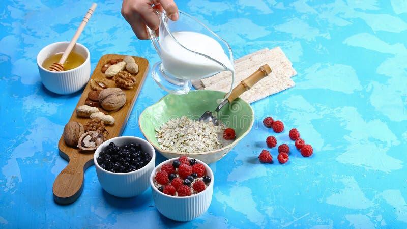 Zdrowy śniadaniowy Oatmeal wypełnia z mlekiem, crispbread, czerwonym rodzynkiem, malinkami, miodem, dokrętkami i czarnymi jagodam obraz stock