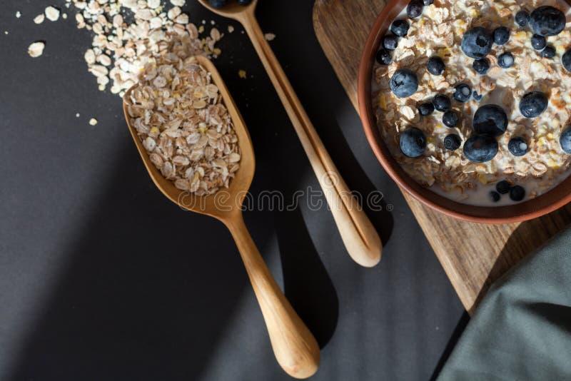 Zdrowy śniadaniowy owsa granola z świeżymi czarnymi jagodami i rodzynki w glinianym pucharze nad ciemnym grunge ukazujemy się Odg fotografia stock