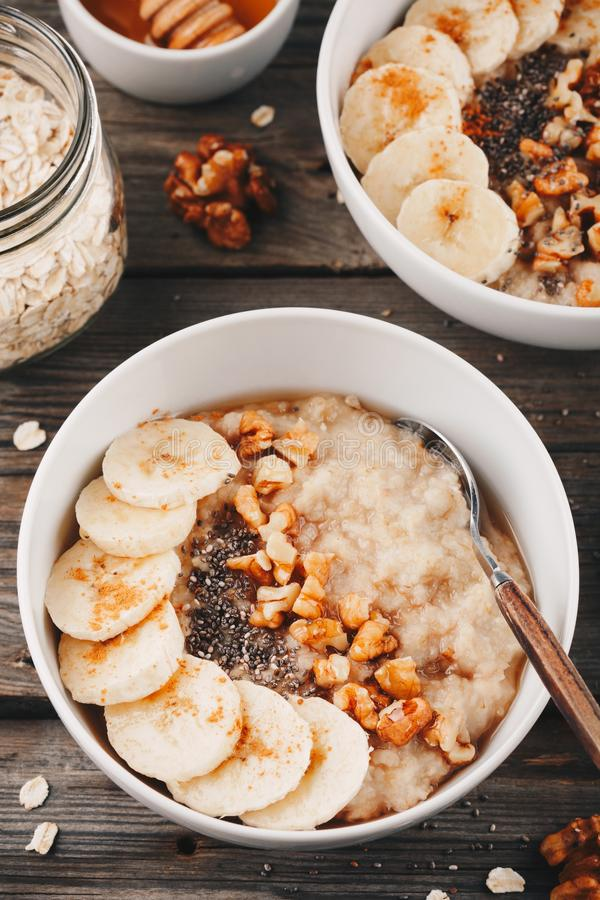 Zdrowy śniadaniowy puchar oatmeal z bananem, orzechami włoskimi, chia ziarnami i miodem, zdjęcia stock