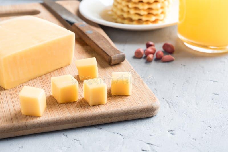 Zdrowy Śniadaniowy ser na desce ciie w sześcianu soku arachidów gofra ciastek Selekcyjną ostrość obrazy royalty free