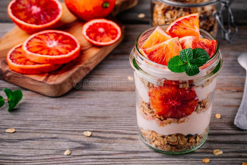 Zdrowy śniadaniowy szklany słoju jogurtu parfait z domowej roboty granola i krwionośną pomarańcze na drewnianym tle obrazy stock