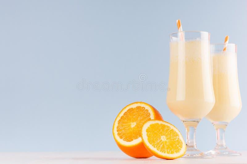 Zdrowy świeży pomarańcze smoothie z cukierki pokrajać pomarańcze, pasiasta słoma na pastelowym błękitnym tle, kopii przestrzeń zdjęcia stock