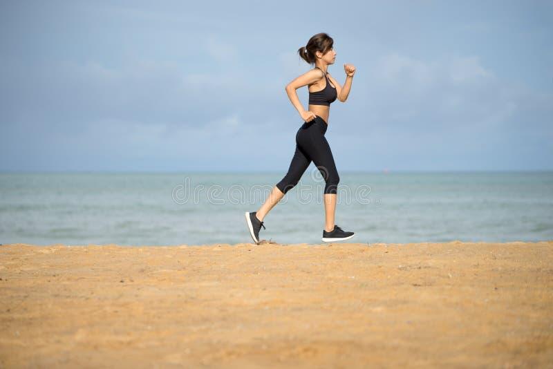 Zdrowy aktywny styl życia Potomstwa bawją się sprawności fizycznej kobiety bieg na plaży przy zmierzchem fotografia royalty free