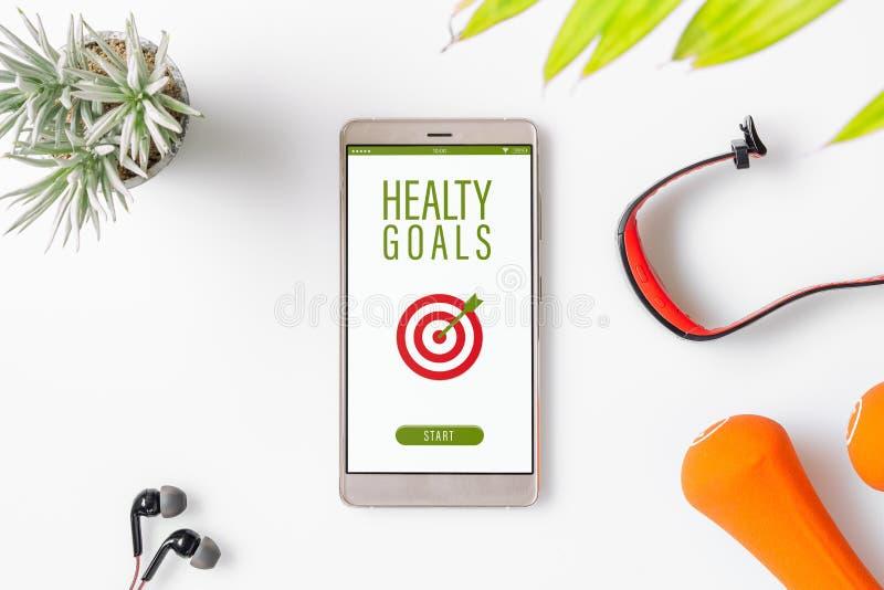 Zdrowy celu pojęcie Sprawność fizyczna zdrowi cele z mockup telefonem komórkowym na bielu stole z dumbbells, mądrze zegarek, słuc obrazy stock