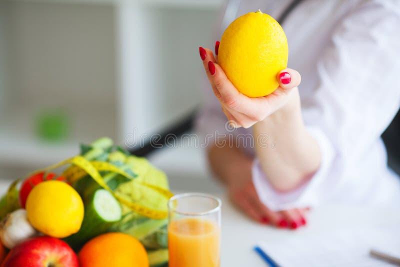zdrowy Doktorska dietetyczka Uśmiecha się cytrynę i Pokazuje Kobieta Trzyma Fru fotografia stock