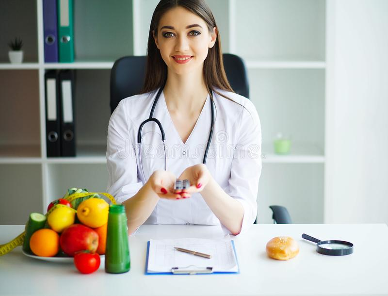zdrowy Doktorska dietetyczka z Pięknym uśmiechem Lekarka Siedzi w Lekkim pokoju przy stołem warzywa świeże owoce zdjęcie stock