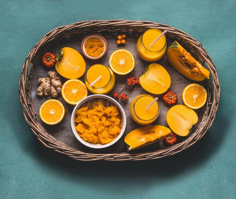 Zdrowy dyniowy smoothie w szkłach z pomarańczowymi kolorów składnikami: persimmon, proszek, pomarańczowy owoc, imbiru i turmeric, zdjęcie stock