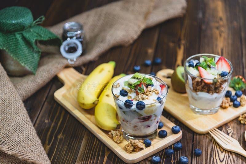 Zdrowy Grecki jogurt z Granola i mieszanymi jagodami na drewniany sto?owym i wiele owoc Karmowy i deserowy poj?cie zdjęcia royalty free