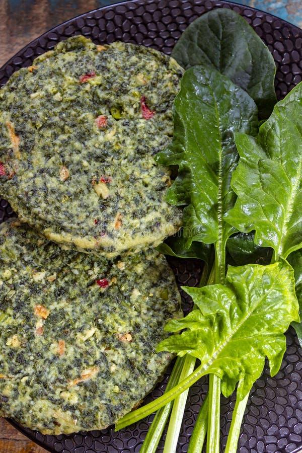 Zdrowy jarosza lub weganinu jedzenie, uncooked zieleni szpinak?w hamburgery, sk?adnik dla hamburger?w fotografia stock