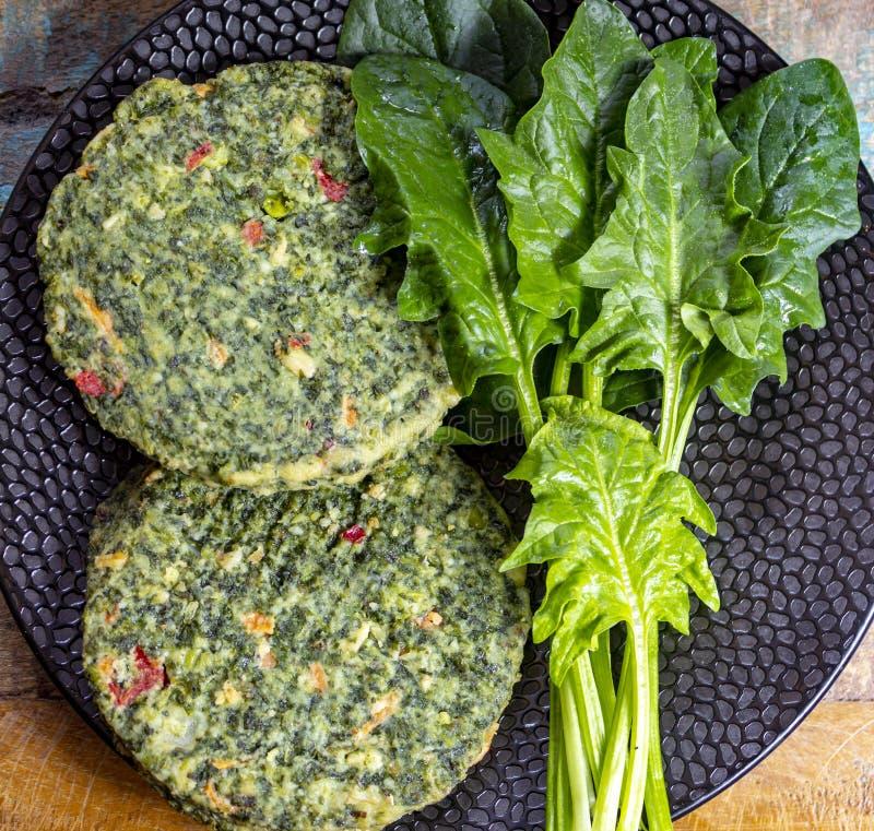 Zdrowy jarosza lub weganinu jedzenie, uncooked zieleni szpinak?w hamburgery, sk?adnik dla hamburger?w obraz royalty free