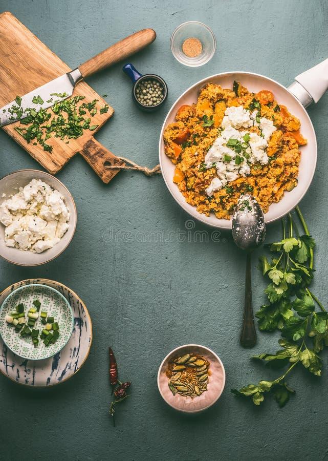 Zdrowy jarski couscous garnek, puchary z składnikami i: warzywa, ziele i feta ser na ciemnym tle, odgórny widok obrazy royalty free