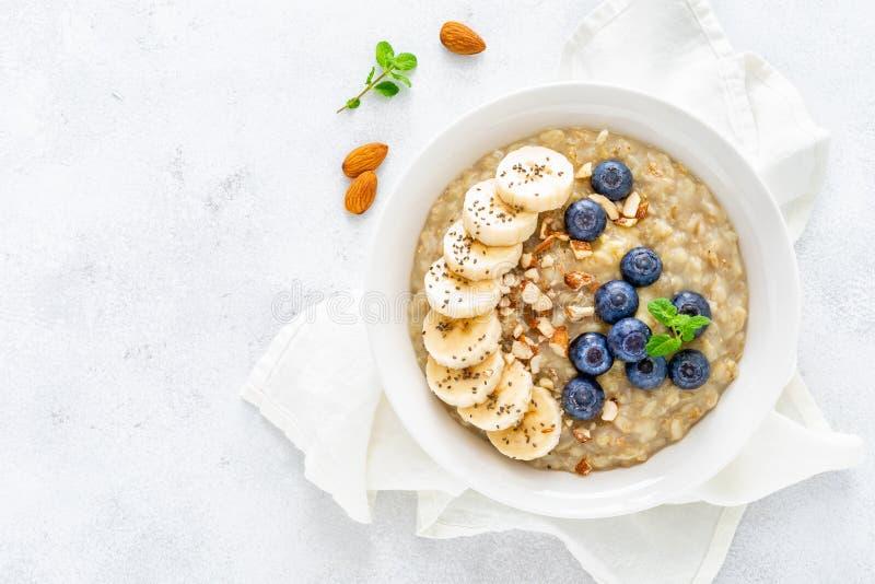 Zdrowy jarski jedzenie, oatmeal z świeżą czarną jagodą, banan, migdałowe dokrętki i chia ziarna dla śniadania, fotografia stock