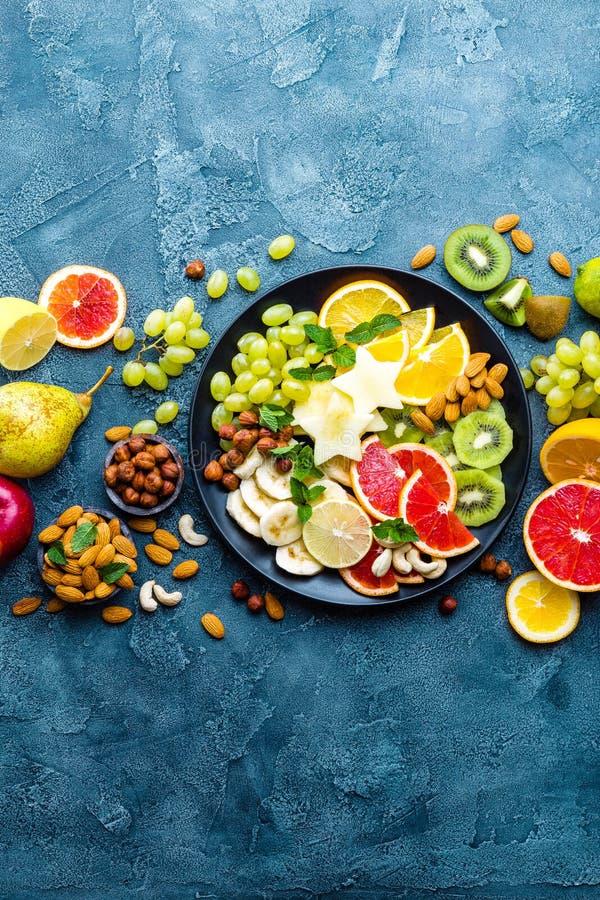 Zdrowy jarski pucharu naczynie z świeżymi owoc i dokrętkami Talerz z surowym jabłkiem, pomarańcze bananowa, grapefruitowy, kiwi,  obraz stock