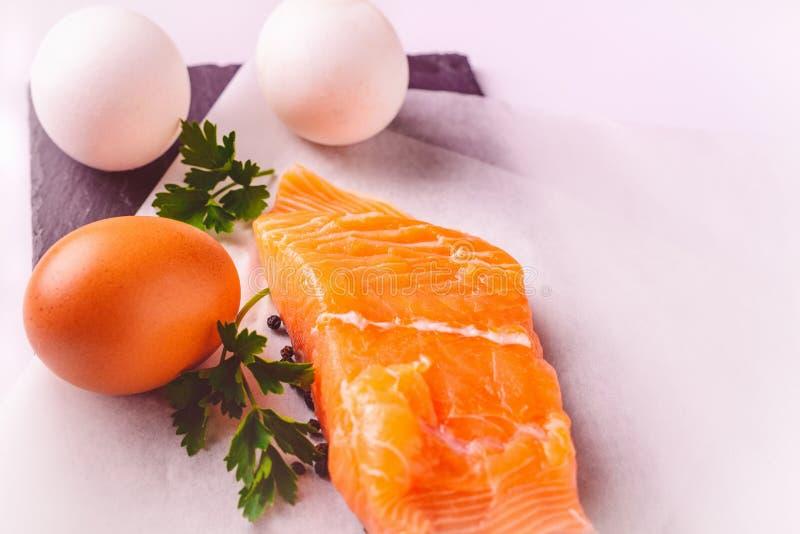 Zdrowy jedzenia, protein, kucharstwa i diety pojęcie, - zamyka up łosoś polędwicowy, jajka i pietruszka na białym tle, zdjęcie stock