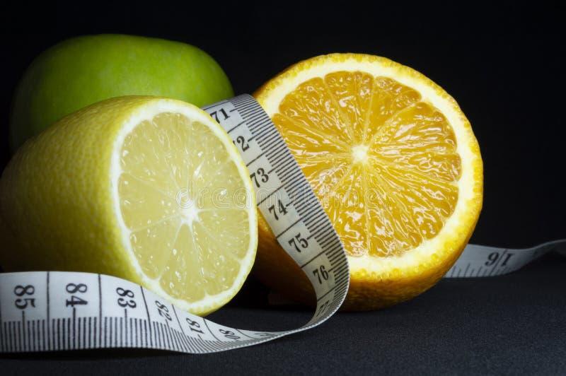 Zdrowy jedzenie: świeża owoc i pomiarowa taśma na czarnym tle obrazy royalty free