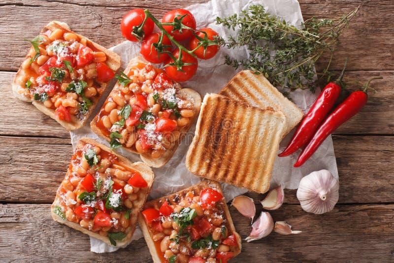 Zdrowy jedzenie: grzanka z białymi fasolami, pomidorami, serem i garli, zdjęcie royalty free