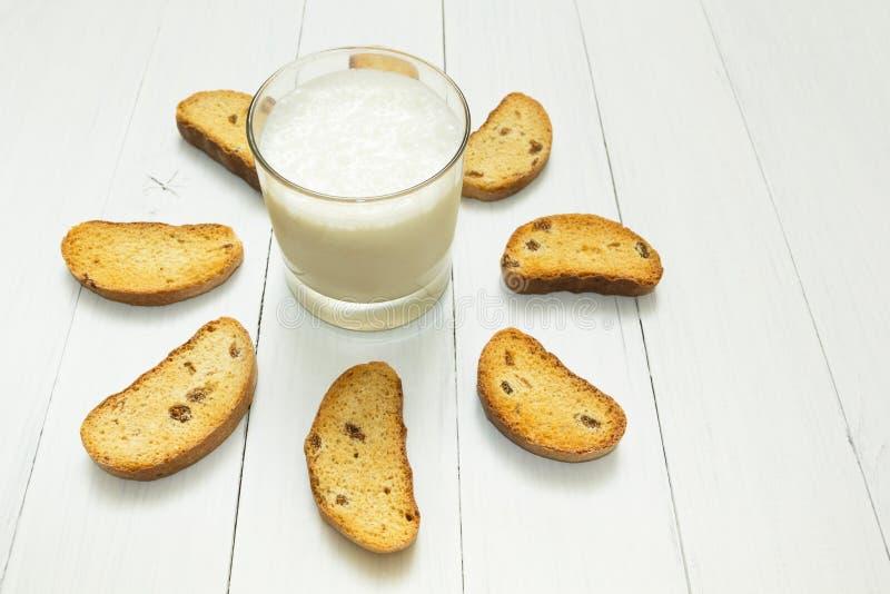 Zdrowy jedzenie, kwaśny jogurt w szklanej filiżance i krakersy z rodzynkami na białym stole, obrazy royalty free