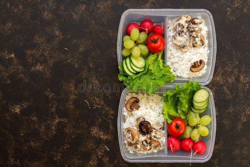 Zdrowy jedzenie w zbiornikach, ryż z pieczarkami i warzywach na ciemnym tle, odgórny widok kosmos kopii fotografia stock